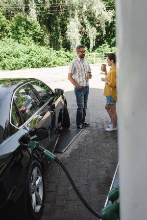 Selektywne skupienie uśmiechniętego mężczyzny trzymającego kawę, aby zbliżyć się do żony podczas tankowania samochodu na stacji benzynowej