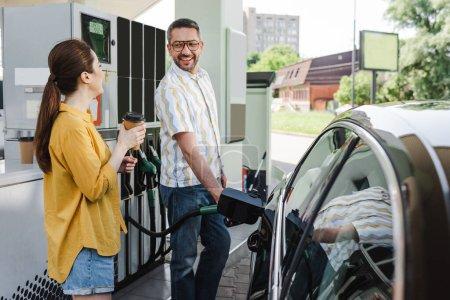 Selektywne skupienie uśmiechniętego mężczyzny patrzącego na żonę z kawą na wynos podczas tankowania samochodu na stacji benzynowej