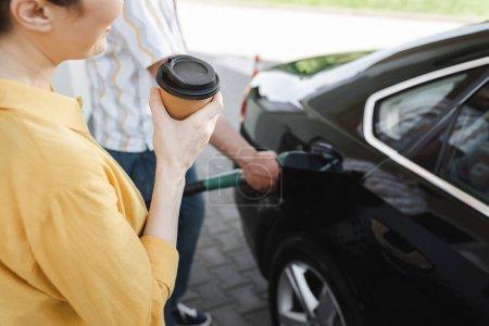 Photo pour Vue recadrée de la femme tenant du café pour aller tandis que le mari ravitaillement automatique sur la station-service - image libre de droit