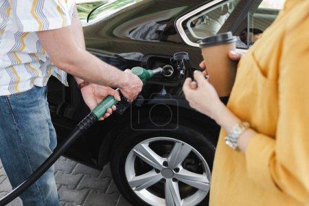 Widok człowieka trzymającego dyszę paliwową w pobliżu zbiornika paliwa samochodu w pobliżu kobiety z papierową filiżanką na stacji benzynowej