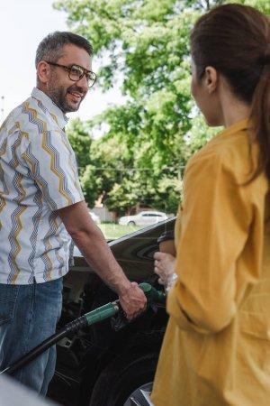 Selektywne skupienie się na uśmiechniętym człowieku tankującym samochód i patrzącym na żonę z papierową filiżanką na stacji benzynowej