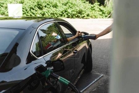 Selektywne skupienie pracowników stacji paliw posiadających terminal płatniczy w pobliżu kobiety z kartą kredytową w samochodzie