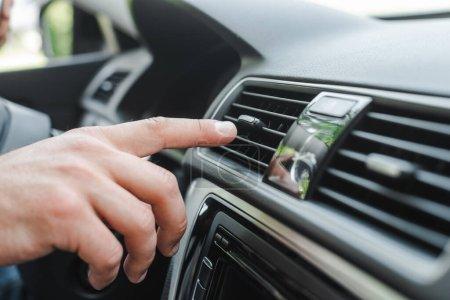Photo pour Vue recadrée de l'homme ajustant le climatiseur sur le tableau de bord en auto - image libre de droit