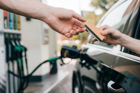 Photo pour Vue recadrée de la femme donnant carte de crédit au travailleur de la station-service tout en alimentant l'automobile - image libre de droit