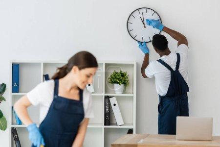 Photo pour Focalisation sélective de nettoyeur afro-américain horloge de nettoyage près de collègue souriant au bureau - image libre de droit