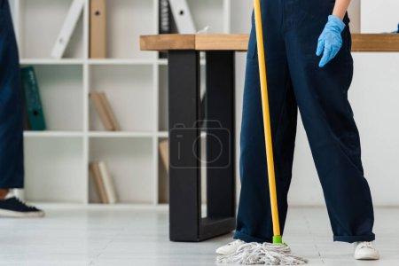 Photo pour Vue recadrée du nettoyant dans le plancher de lavage en gant de caoutchouc avec serpillière dans le bureau - image libre de droit