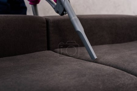 Photo for Cropped view of cleaner using vacuum cleaner on couch - Royalty Free Image