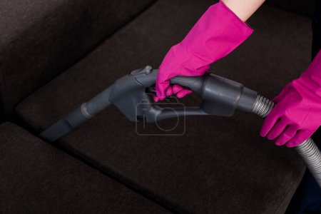 Photo for Cropped view of cleaner in rubber gloves cleaning couch upholstery with vacuum cleaner - Royalty Free Image