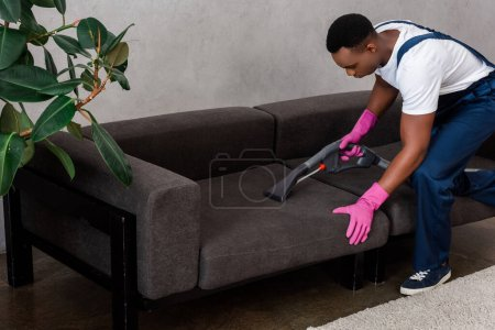Photo for Selective focus of african american cleaner in uniform cleaning upholstery of couch at home - Royalty Free Image