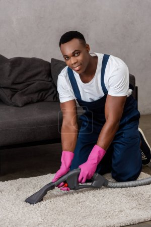 Smiling african american cleaner looking at camera while cleaning carpet at home