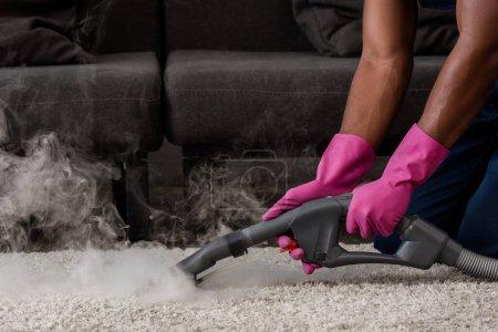 Photo pour Vue recadrée du tapis nettoyant afro-américain avec vapeur chaude - image libre de droit