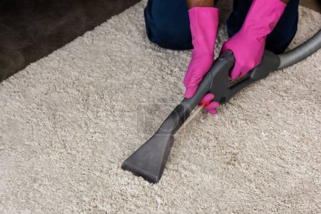 Photo for Cropped view of african american cleaner using vacuum cleaner while cleaning carpet at home - Royalty Free Image