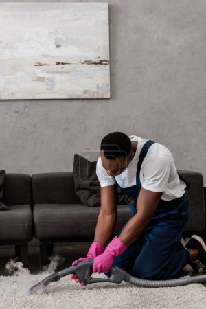 African american cleaner in workwear using vacuum cleaner with hot steam on carpet