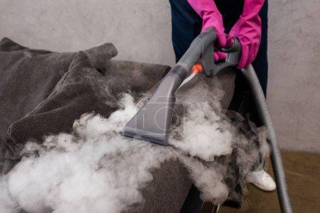 Photo pour Vue recadrée de l'aspirateur dans des gants en caoutchouc à l'aide de vapeur chaude sur le canapé - image libre de droit