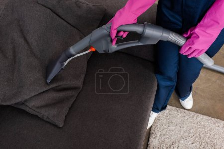 Photo for Cropped view of cleaner in rubber gloves using vacuum cleaner on pillow on couch - Royalty Free Image