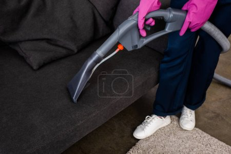 Photo for Cropped view of cleaner in rubber gloves holding vacuum cleaner near couch - Royalty Free Image