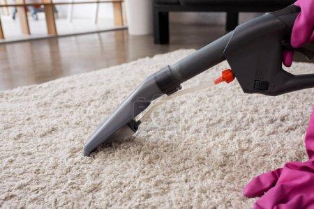 Foto de Vista recortada de limpiador en guantes de goma alfombra de limpieza en casa - Imagen libre de derechos