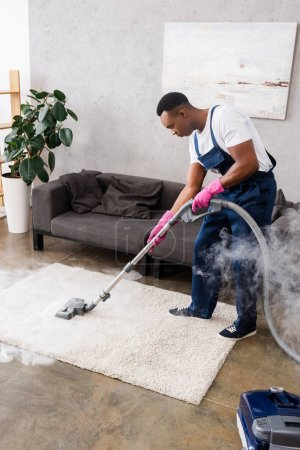 African american cleaner vacuuming carpet with hot steam in living room