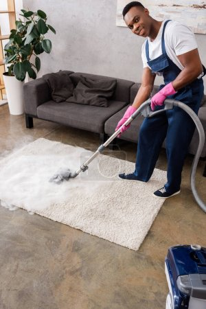 African american cleaner in uniform and rubber gloves smiling at camera while cleaning carpet with hot steam