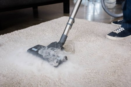 Photo for Cropped view of cleaner using vacuum cleaner with hot steam on carpet at home - Royalty Free Image