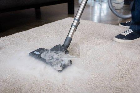 Photo pour Vue recadrée du nettoyeur à l'aide d'aspirateur à vapeur chaude sur tapis à la maison - image libre de droit