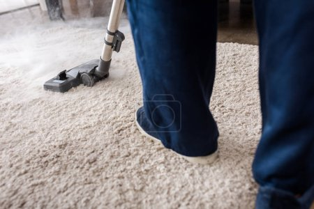 Photo for Cropped view of cleaner using vacuum cleaner with hot steam on carpet in living room - Royalty Free Image