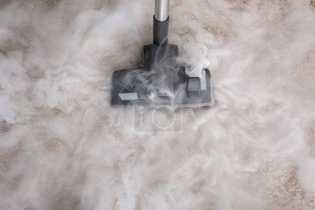 Photo pour Vue de dessus de la vapeur chaude près de la brosse d'aspirateur sur le tapis à la maison - image libre de droit