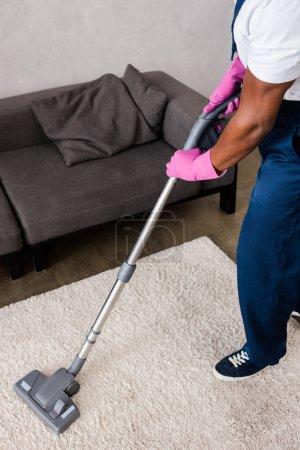 Foto de Vista recortada del limpiador afroamericano en uniforme usando aspiradora en casa - Imagen libre de derechos