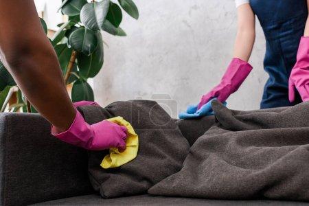 Foto de Vista recortada de limpiadores multiétnicos limpieza almohadas tapicería en el sofá - Imagen libre de derechos