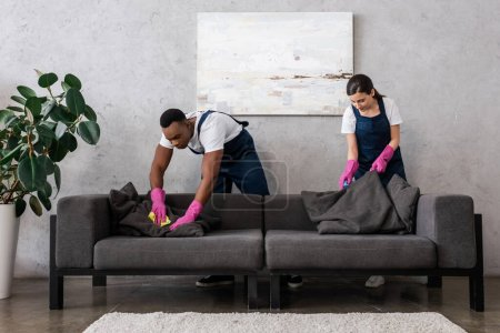 Photo for Multicultural cleaners in uniform cleaning couch with rags in living room - Royalty Free Image