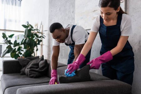 Photo for Selective focus of multiethnic cleaners cleaning couch upholstery with rags at home - Royalty Free Image