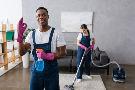 Photo for Selective focus of smiling african american cleaner showing okay and holding detergent near colleague using vacuum cleaner - Royalty Free Image