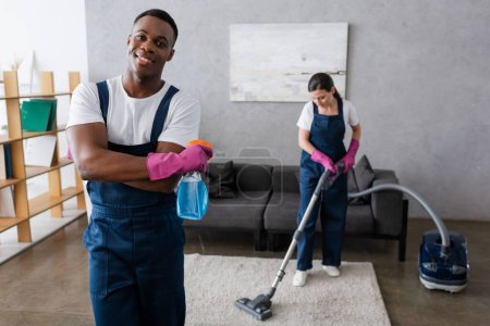 Photo for Selective focus of african american cleaner holding detergent and smiling at camera near colleague cleaning carpet - Royalty Free Image
