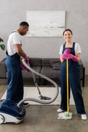 Photo for Smiling cleaner holding mop near african american colleague cleaning carpet at home - Royalty Free Image