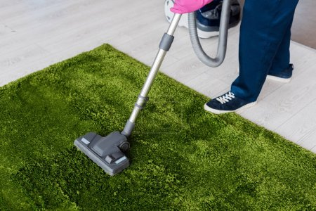 Photo for Cropped view of cleaner using vacuum cleaner on green carpet - Royalty Free Image