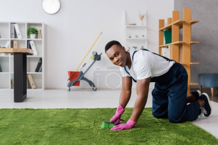 Photo for Smiling african american cleaner holding brush while cleaning carpet in office - Royalty Free Image