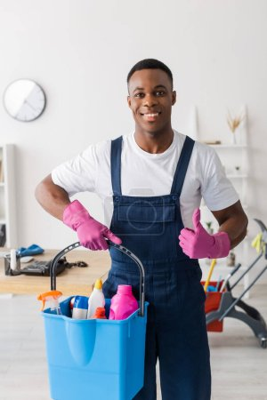 Smiling african american cleaner in uniform showing like and holding bucket of cleaning supplies in office