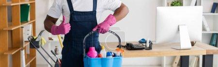 Photo pour Récolte panoramique de nettoyant afro-américain en uniforme montrant comme et tenant des fournitures de nettoyage dans le seau dans le bureau - image libre de droit