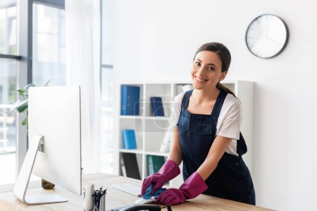 Photo for Selective focus of cleaner smiling at camera while cleaning computer mouse on table in office - Royalty Free Image