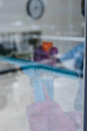 Foto de Enfoque selectivo del limpiador con mango de escobilla y detergente mientras limpia la ventana en la oficina - Imagen libre de derechos