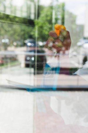 Photo pour Concentration sélective du nettoyant à l'aide d'un détergent et d'une poignée de raclette lors du nettoyage du verre de la fenêtre - image libre de droit
