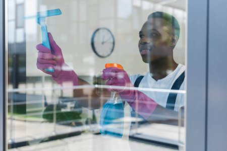 Photo for Selective focus of african american cleaner in rubber gloves using detergent and squeegee handle while cleaning window - Royalty Free Image