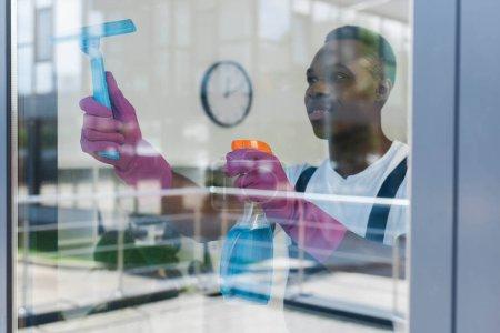 Photo pour Concentration sélective du nettoyant afro-américain dans les gants en caoutchouc en utilisant un détergent et une poignée de raclette pendant le nettoyage de la fenêtre - image libre de droit