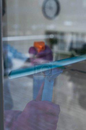 Foto de Enfoque selectivo del limpiador con mango de escobilla y detergente en la ventana - Imagen libre de derechos