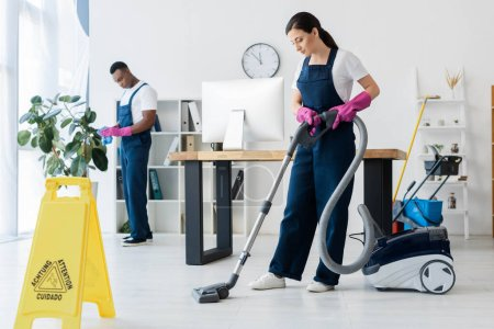 Photo for Selective focus of cleaner using vacuum cleaner near wet floor sign and african american colleague in office - Royalty Free Image