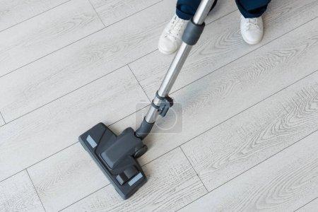 Photo pour Vue recadrée du nettoyeur à l'aide d'aspirateur sur le sol - image libre de droit