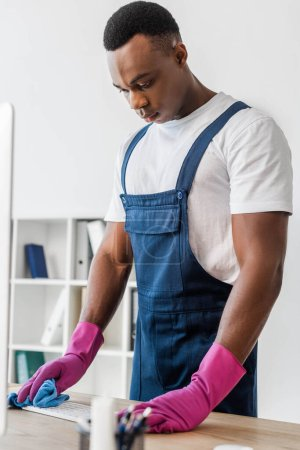 Photo for Selective focus of african american cleaner in overalls cleaning computer keyboard in office - Royalty Free Image