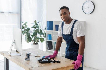 Photo pour Nettoyant afro-américain souriant avec chiffon debout près de la table de bureau - image libre de droit