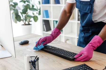 Photo for Cropped view of african american cleaner in rubber gloves cleaning computer keyboard on office table - Royalty Free Image