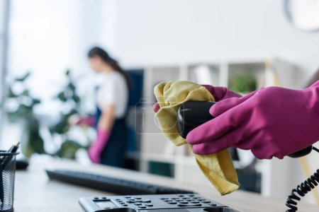Photo for Selective focus of cleaner in rubber gloves cleaning telephone near colleague in office - Royalty Free Image